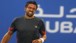 Serbia's Tipsarevic reacts after hitting a return to Britain's Murray during match at Abu Dhabi Tennis Championships in Abu Dhabi